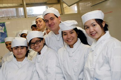 Students in chef outfit in a group posing for picture
